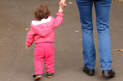 Child hold hands and walks in the park with his mother Royalty Free Stock Photos