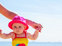Child holding adult hands on beach Royalty Free Stock Image