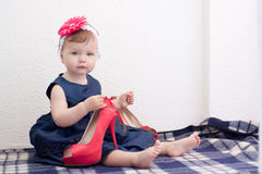 Child is holding adult high heel shoe. Child is holding an adult shoe Stock Image