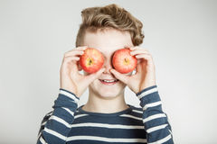 Child holding apples in front of his eyes Royalty Free Stock Image