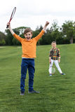 Child holding badminton racquet and triumphing while sibling standing behind. Happy child holding badminton racquet and triumphing while sibling standing behind stock photography