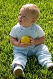 Child holding ball. Close up of cute young boy sat on grass holding ball Royalty Free Stock Photography