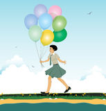 Child holding balloons. Girl holding balloons running on the road Stock Image