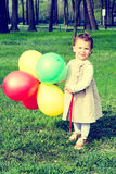 Child holding balloons Stock Photography