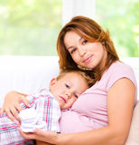 Child holding belly of pregnant woman Stock Photography