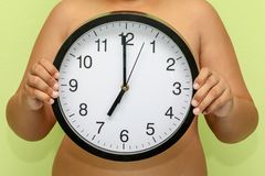 Child holding big clock showing. 7 o`clock Royalty Free Stock Image