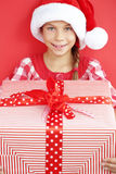 Child holding big gift. Portrait of a 7 years old child holding big Christmas gift box on red background Stock Photography
