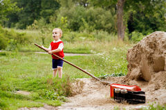 A child holding a big shovel, he opened his mouth with delight. Royalty Free Stock Photos