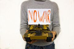 Child holding a big toy tank. A child holding a big toy tank with a sign no war on white background Stock Images