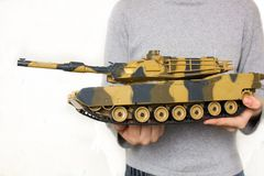 Child holding a big toy tank Stock Photo