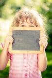 Child holding blackboard blank Royalty Free Stock Photography