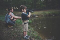 Child Holding Blue and Black Fishing Rod Beside Body of Water Royalty Free Stock Photography