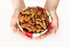 Child holding a bowl of almonds. Shot of a child holding a bowl of almonds Stock Image