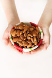 Child holding a bowl of almonds vertical Royalty Free Stock Photo