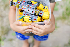 Child holding box with toys on outdoors background Stock Photos