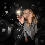 Child Holding Bright Light Bulb on Black Background. A child is holding up a bright glowing lightbulb with dark light bulbs around her on an black background for stock photo