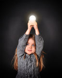 Child holding Bright Light Bulb. A little child is holding a bright glowing lightbulb on an black background for an education or academic concept stock image