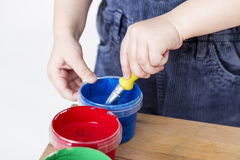 Child holding brush in paint tub Royalty Free Stock Photos