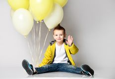 Child holding the bunch of balloons staying on the knee over the white background royalty free stock photography
