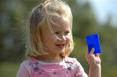Child holding card. Little caucasian white blond girl head portrait with cute expression in the pretty face and blue eyes holding a blank blue card in her little Stock Photo