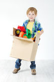 Child holding cardboard box packed with toys. Moving and growing concept Royalty Free Stock Photo