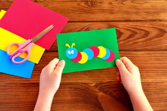 Child holding a caterpillar card. Summer paper crafts Stock Photos