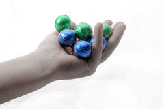 A child holding chocolate balls wrapped in colourful foil. Image of a child holding chocolates Stock Photos