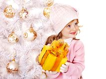 Child holding Christmas gift box. Child in hat and mittens holding gold gift box near white Christmas tree. Isolated Stock Image