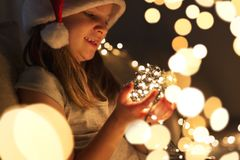 Child holding Christmas lights. Beautiful little girl sitting on a living room couch, wearing Santa`s hat and holding bunch of Christmas lights; child setting up royalty free stock photos
