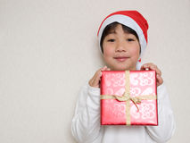 Child holding Christmas present. Child wearing Santa hat holding Christmas present Royalty Free Stock Images