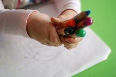 Child holding crayons stock image