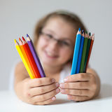 Child holding crayons. Portrait of child holding crayons before face Royalty Free Stock Photos