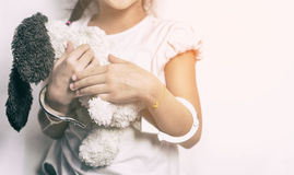 Child holding a doll with her hand in handcuffed Royalty Free Stock Image