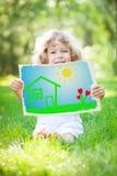 Child holding drawn spring landscape Stock Photo