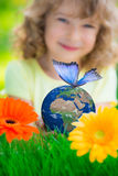 Child holding Earth planet with blue butterfly in hands. Against green spring background. Elements of this image furnished by NASA stock photos