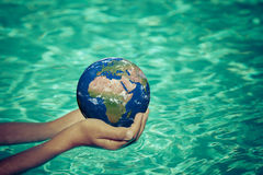 Child holding Earth planet in hands Royalty Free Stock Photos