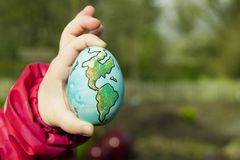 Child holding an egg with Planet Earth painted on it on a sunny Stock Images