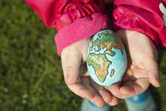 Child holding an egg with Planet Earth painted on it on a sunny Stock Photos