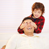 Child holding eyes of father closed. Child holding eyes of his laughing father closed royalty free stock images