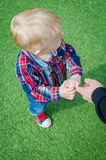 Child holding father's hand. Stylish hipster toddler in sneakers, jeans and shirt standing and holding father's finger. A parent holds the hands of a little baby Stock Photos