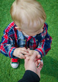 Child holding father's hand. Stylish hipster toddler in sneakers, jeans and shirt standing and holding father's finger. A parent holds the hands of a little baby Stock Images