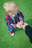 Child holding father's hand. Stylish hipster toddler in sneakers, jeans and shirt standing and holding father's finger. A parent holds the hands of a little baby Royalty Free Stock Photography