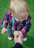 Child holding father's hand. Stylish hipster toddler in sneakers, jeans and shirt standing and holding father's finger. A parent holds the hands of a little baby Royalty Free Stock Images
