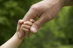 Child holding fathers hand. Going together Royalty Free Stock Photo
