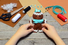 Child holding a felt gingerbread man in his hands. Christmas tree gingerbread man ornament, sewing supplies on old wooden table Royalty Free Stock Images