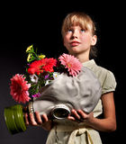 Child holding flowers and gas mask . Stock Photo