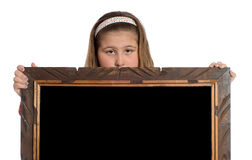 Child Holding Frame. A preteen girl holding a wooden frame with a black interior isolated against a white background stock photo