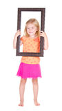 Child holding frame around face Stock Image