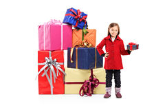 Child holding a gift. Full length portrait of a child holding a gift and posing next to a pile of gifts isolated on white background Stock Photography