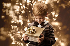 Child holding gift box, boy in vintage style. Stock Photo